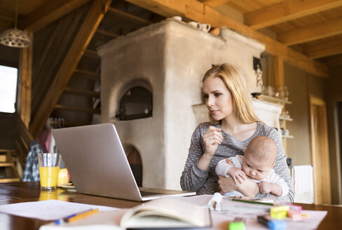 Mother with baby at home using laptop - HAPF01382