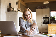 Mother with baby at home using laptop and taking notes - HAPF01385