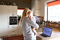 Mother with baby at home looking at house on laptop screen - HAPF01397