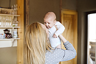Mother lifting up baby at home - HAPF01403