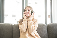 Happy young woman listening to music at home - SIPF01524