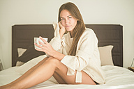 Portrait of young woman sitting on bed with cup of coffee - SIPF01536