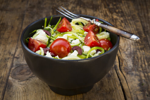 Bowl of zucchini spaghetti with feta, cherry tomatoes and black olives on wood - LVF05982