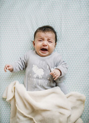 Portrait of crying baby girl lying on bed - GEMF01554