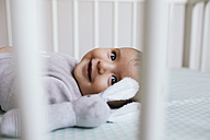Smiling baby girl lying in crib with toy bunny - GEMF01560