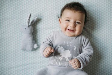Portrait of smiling baby girl lying on bed beside toy bunny - GEMF01563