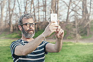 Bearded man taking selfie with smartphone - RTBF00789