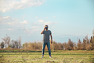 Man standing on a meadow taking photo with vintage camera - RTBF00798