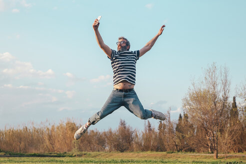 Man jumping in the air while taking photo with smartphone - RTBF00801