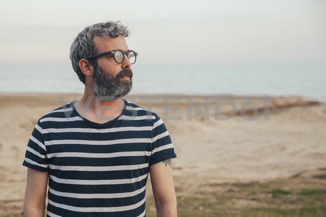 Portrait of bearded man on the beach looking at distance - RTBF00804