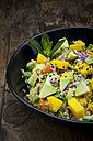 Bowl of quinoa salad with mango, avocado, tomatoes, cucumber, herbs and black sesame - LVF05985