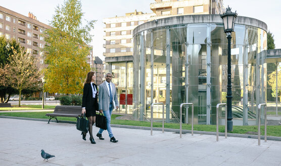Young businessman and woman walking in the city - DAPF00613