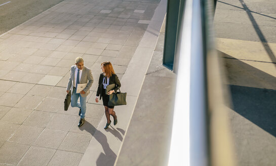 Young businessman and woman walking in the city - DAPF00622