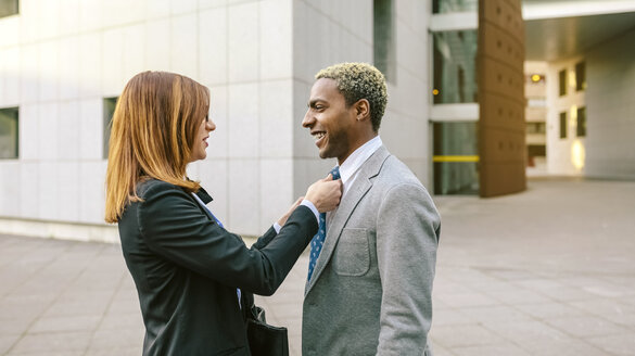 Young businesswoman fastening tie of young businessman - DAPF00631