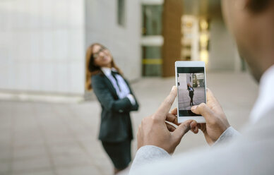 Young businessman and woman taking smart phone pictures - DAPF00634