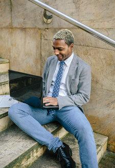 businessman sitting on stairs, using laptop - DAPF00643