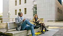Young businessman and woman sitting on bench, talking - DAPF00646