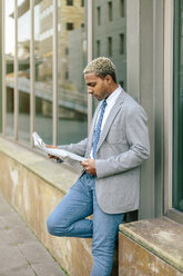 Businessman leaning against wall, reading newspaper - DAPF00649
