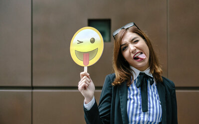 Businesswoman holding emoji smiling with tongue sticking out - DAPF00670