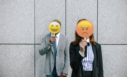 Young businessman and woman covering faces with emoji masks - DAPF00673