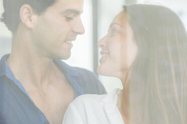 Smiling young couple in love behind windowpane - SIPF01572