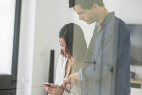 Young couple in love looking at cell phone at home - SIPF01578