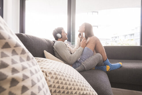 Happy young couple with headphones and smartphone on couch - SIPF01593