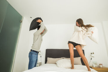 Playful young couple having a pillow fight at home - SIPF01599