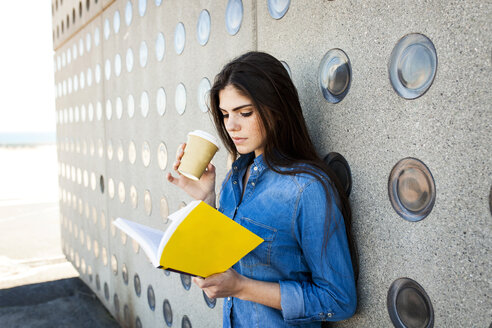 Young woman with coffee to go reading book - VABF01294