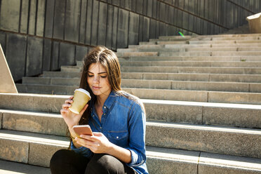Young woman with coffee to go sitting on stairs looking at cell phone - VABF01297