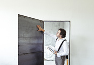 Architect checking steel door at construction site - REAF00250