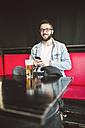 Portrait of smiling young man sitting in a pub - RAEF01809