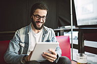 Portrait of smiling young man sitting in a pub using tablet - RAEF01812