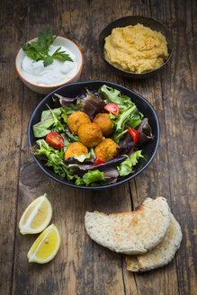 Bowls of mixed salad, tomatoes, sweet patato Falafel and Hummus, yoghurt sauce and flat bread - LVF06010
