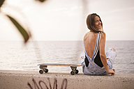 Smiling young woman with skateboard sitting on a wall in front of the sea - SIPF01609