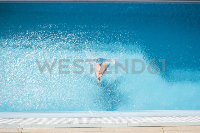 Woman jumping into swimming pool - SIPF01621