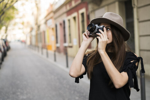 Young woman taking pictures with camera outdoors - KKAF00642