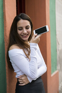 Portrait of smiling young woman with cell phone - KKAF00648