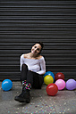 Smiling young woman sitting on pavement with balloons - KKAF00654
