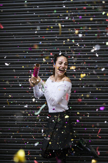 Happy young woman standing in front of black roller shutter throwing confetti - KKAF00657