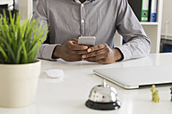 Close-up of businessman at desk using smartphone - MOMF00035