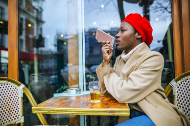 Young woman in Paris sitting in cafe and leaving a voice message - KIJF01367