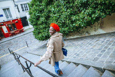 Young woman in Paris walking on stairs - KIJF01370