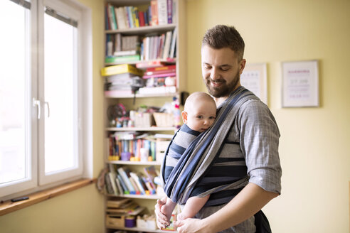 Father with baby son in sling at home - HAPF01408