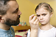 Father at home caring for daughter having chickenpox - HAPF01426