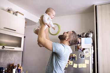 Father holding baby son in kitchen - HAPF01438
