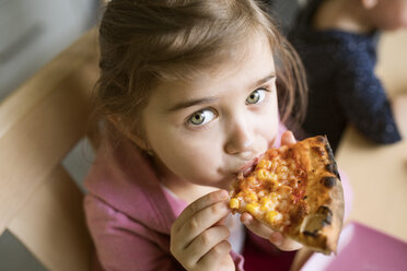 Little girl at home eating slice of pizza - HAPF01447