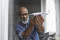 Mature man plying with paper plane - FMKF03738
