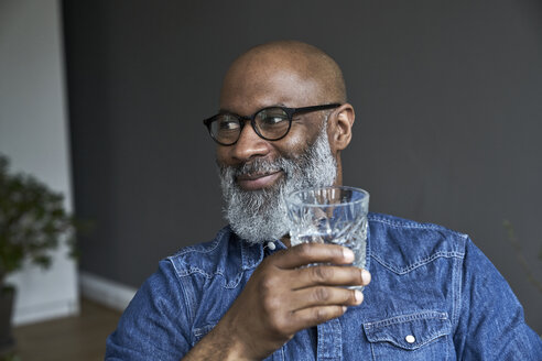 Mature man holding glass of water - FMKF03741