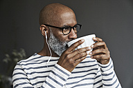 Mature man with earphones drinking coffee - FMKF03747